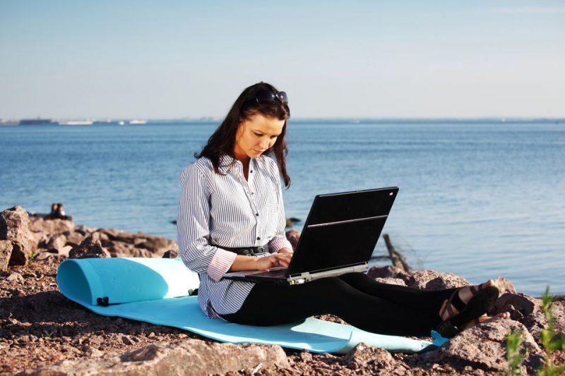 Девушка у моря работает за ноутбуком