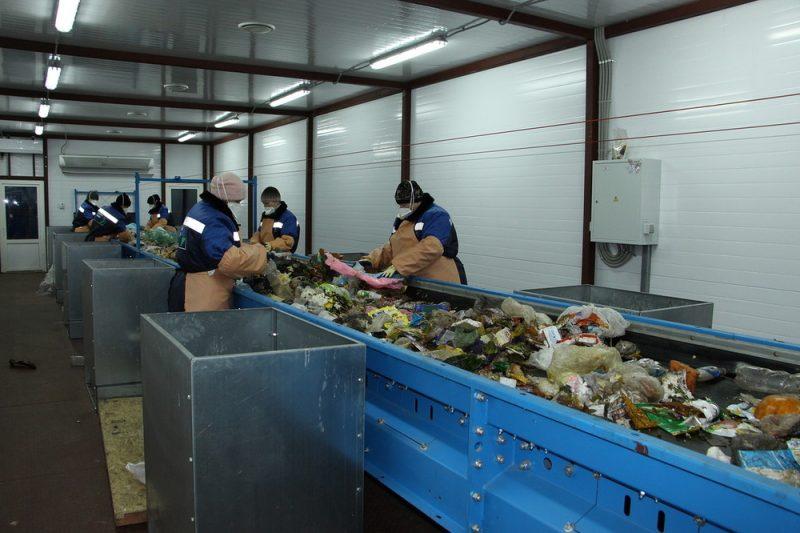 Люди сортируют мусор на мусороперерабатывающем заводе