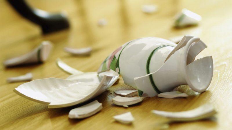 Разбитая белая ваза на полу