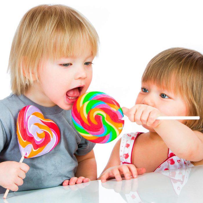 Двое детей с цветными леденцами на палочке