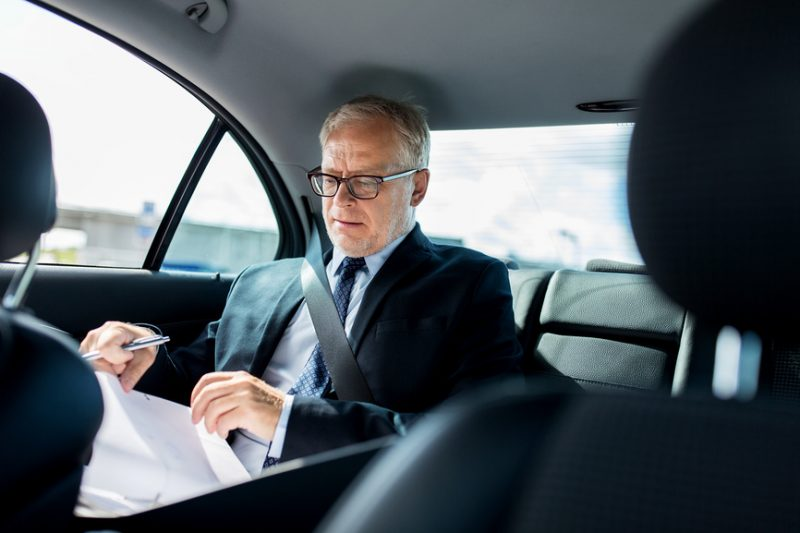 Мужчина с бумагами едет в машине