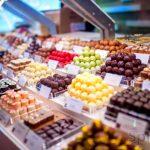 Разнообразие вкусов и цветовой гаммы в конфетах ручной работы на выставочной витрине