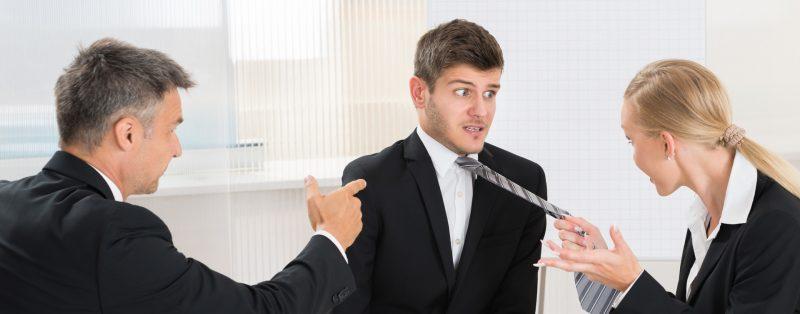 Мужчина и женщина ругают молодого парня, держа его за галстук