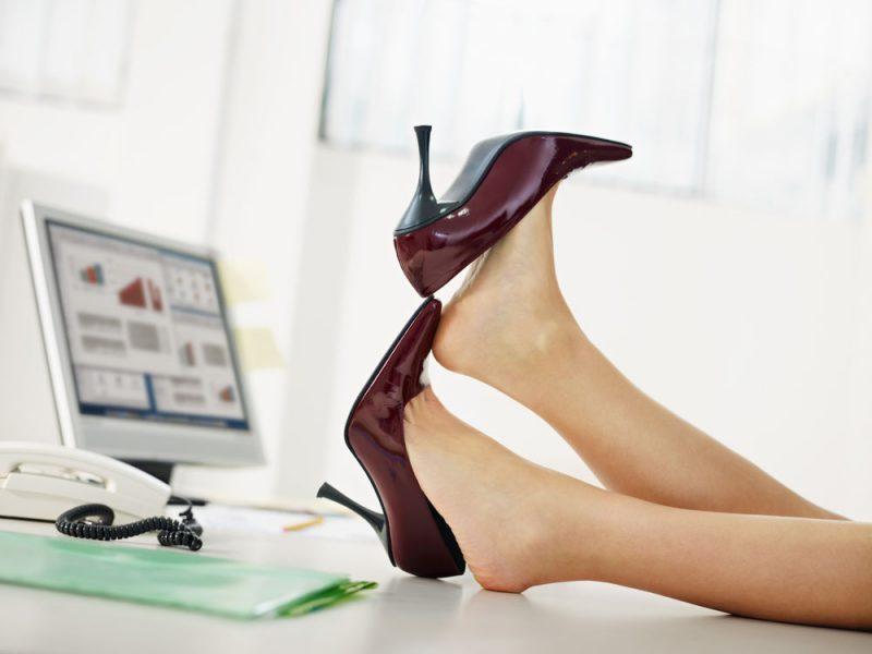 Женские ноги в туфлях на рабочем столе