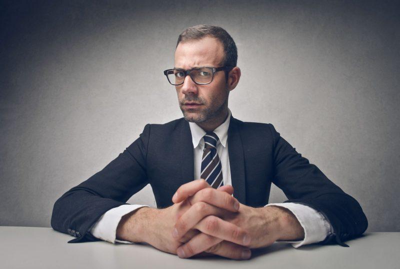 Молодой мужчина в костюме сидит за столом