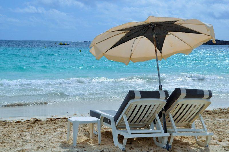 Зонт и шезлонги на фоне моря