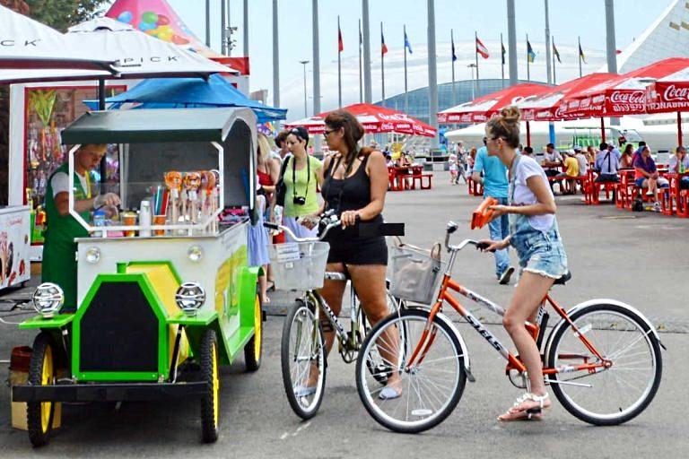 Люди на велосипедах рядом с лотоком с соками и мороженым