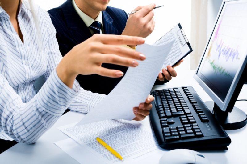 Женщина и мужчина за компьютером с документами
