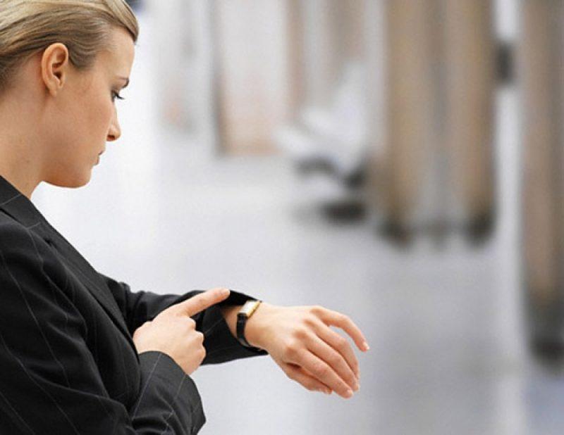 Женщина смотрит на наручные часы