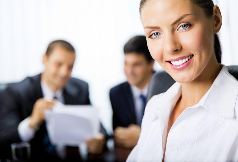 Женщина в офисной одежде на фоне мужчин с документами в руках